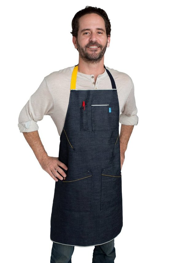 A man wearing a sample of a blue denim apron with yellow accent strap